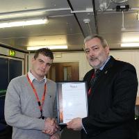 G4S' Luke Pearce receiving the award from the BSIA'S Trevor Elliott